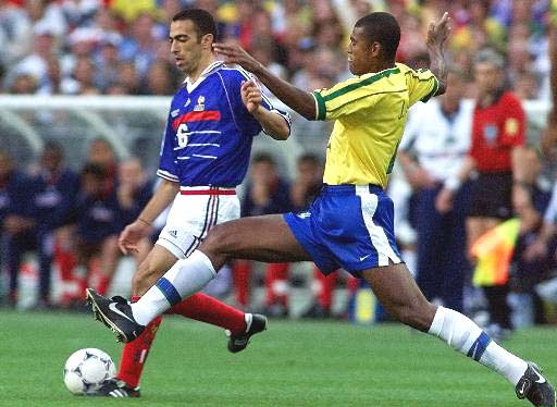 Youri Djorkaeff of France, left, is challenged by Junior Baiano of Brazil during the final of the soccer World Cup 98 between Brazil and France at the Stade de France in Saint Denis, north of Paris, Sunday, July 12, 1998.