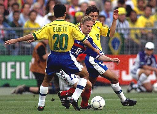 France's Emmanuel Petit dribbles between Brazil's Bebeto and Leonardo during the final of the soccer World Cup 98 between Brazil and France at the Stade de France in Saint Denis, north of Paris, Sunday, July 12, 1998.