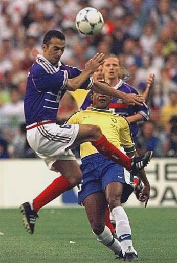 Youri Djorkaeff of France, left, attempts to charge down a clearance from Brazil's Cesar Sampaio during the final of the soccer World Cup 98 between Brazil and France at the Stade de France in Saint Denis, north of Paris, Sunday, July 12, 1998.